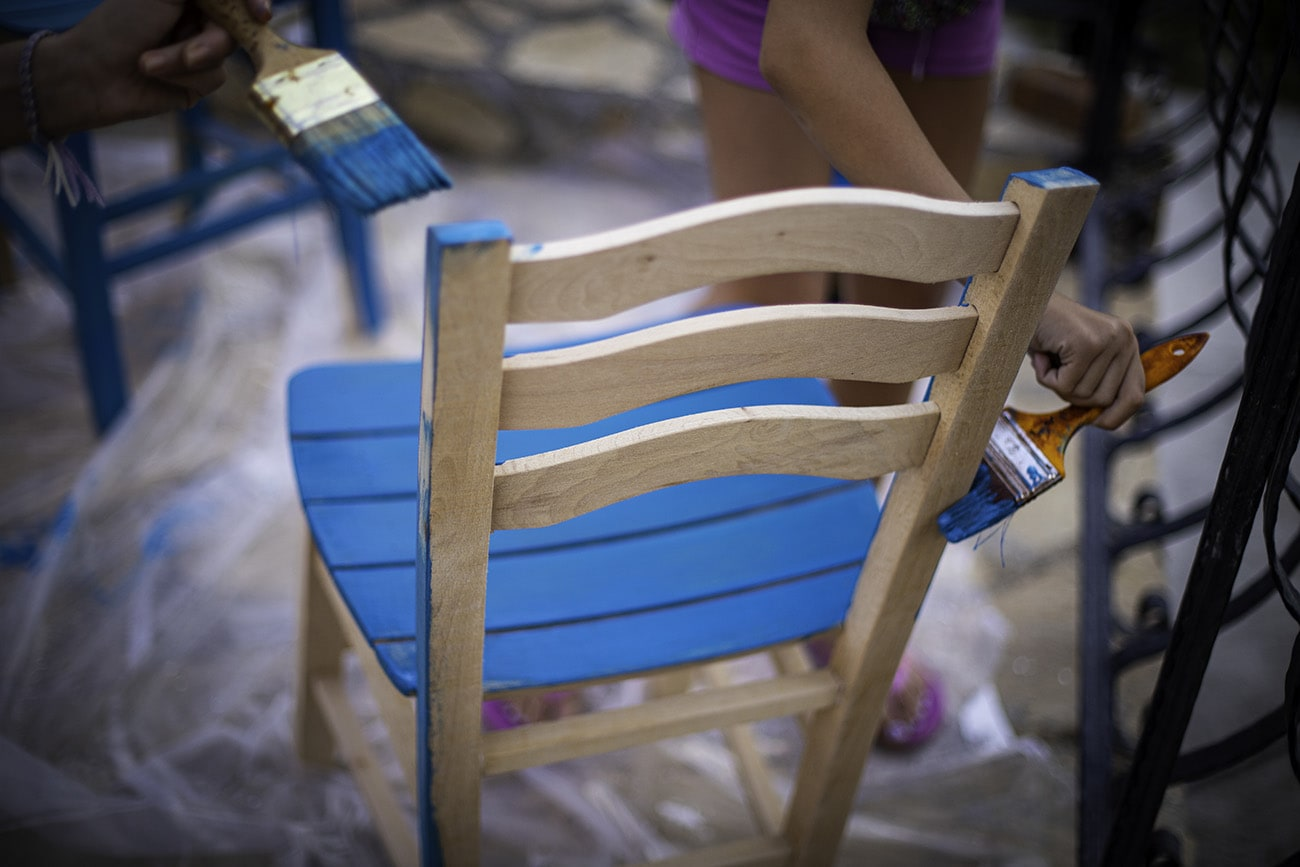 Painting wood chair to blue color at outdoors
