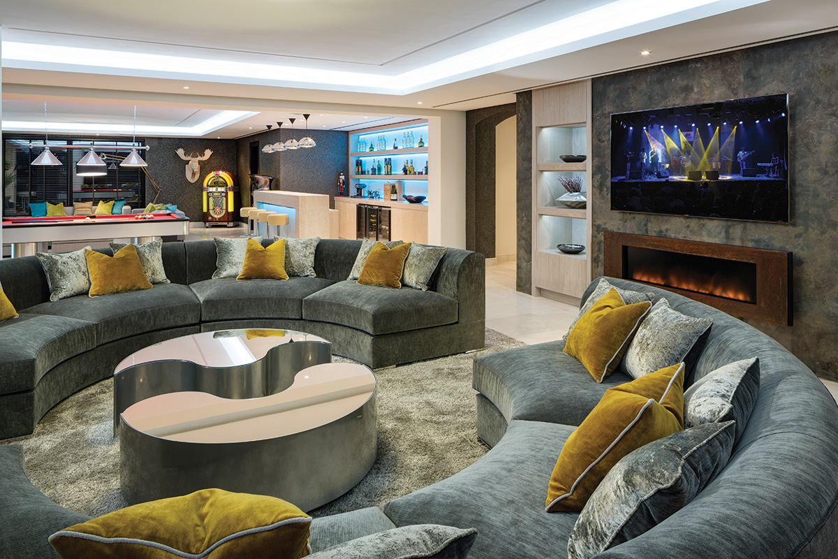 This magnificent entertainment room has two distinct sofa areas, a bar, a pool table and a vintage Juke box