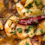 Sizzling hot prawns, drenched in olive oil with plenty of garlic and chilli