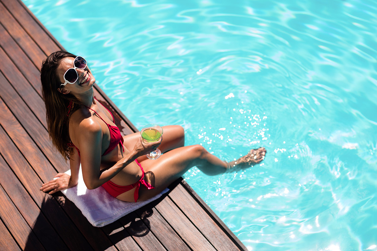 Girl with cocktail sittoing on side of swimming pool