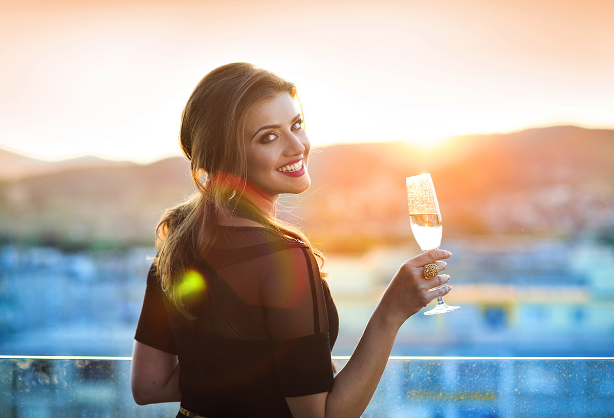 Girl holding a glass of Champagne looking into sunset