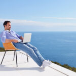 Man sitting on terrace with laptop looking out to sea