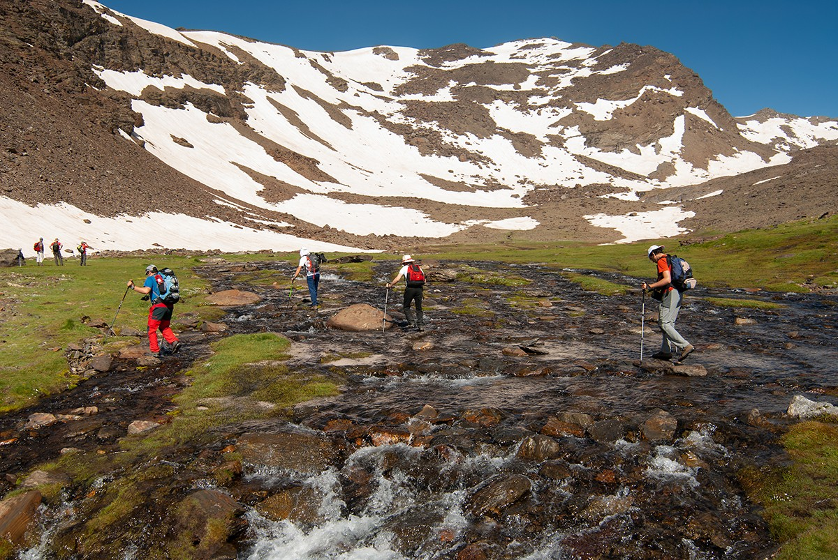 Hikers crossing the channel of the Hondera lagoon in the Sierra Nevada National Park