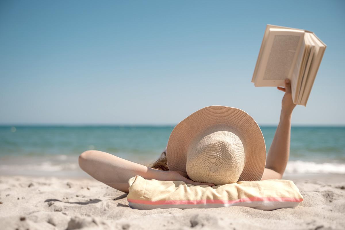 Girl lying on beach reading book