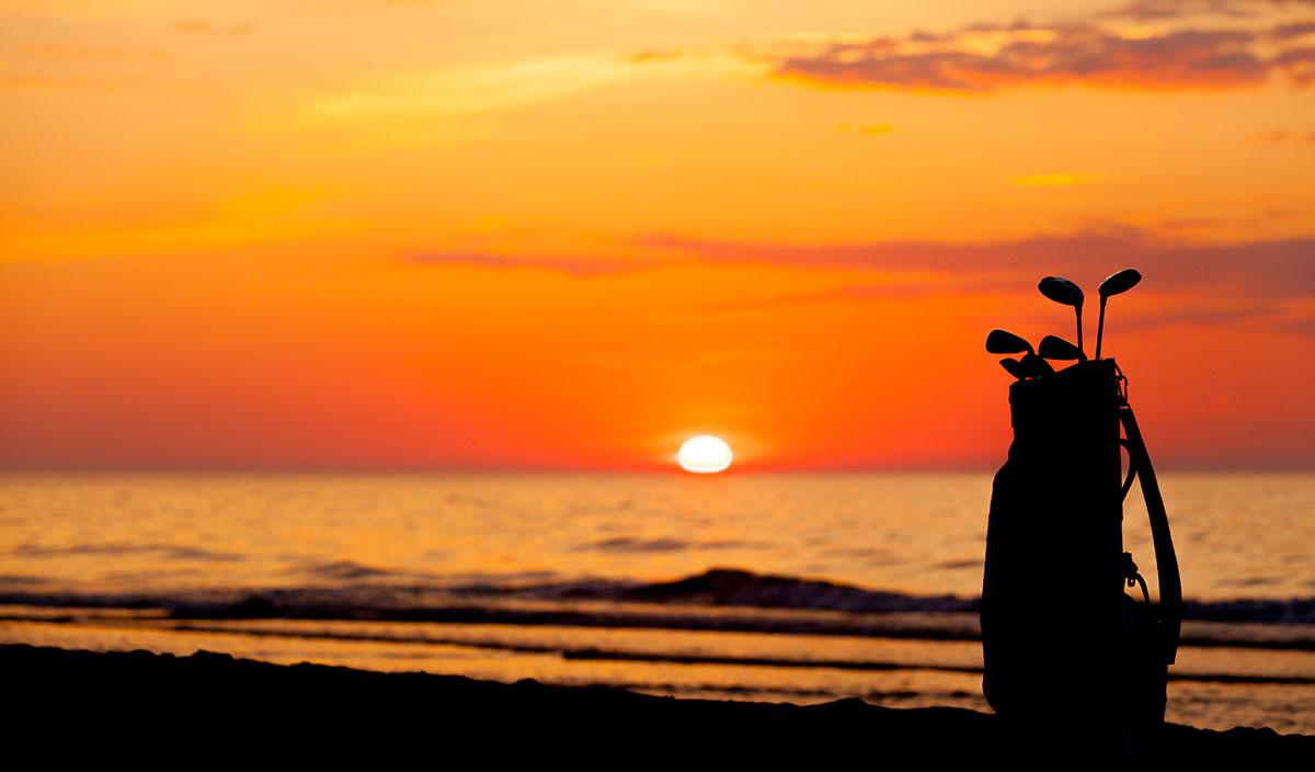 Golf clubs against sunset